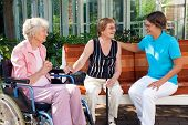 Three Women Sitting Chatting On A Garden Bench