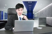 Asian Businessman Drinking Coffee And Working With Computer In Modern Office