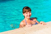 Happy Young Woman Floating In The Pool