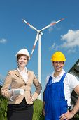 Engineer And Contractor Posing In Front Of Wind Turbine