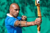 stock photo of archer  - Bowman or archer aiming at target with bow and arrow - JPG