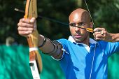 pic of archer  - archer at shooting range with bow and arrow - JPG