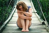 Portrait of pretty sad girl on the bridge