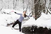 Young Active Pregnant Woman Walking In A Snowy Park