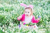 Adorable Toddler Girl Wearing Bunny Ears Playing With Easter Eggs Amoung first white spring flowers