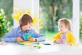 Two Kids  in a bright sunny white dining room a big garden view window