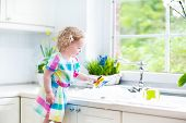 Beautiful Toddler Girl washing dishes, cleaning with a sponge and playing with foam in the sink