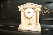 Elegant antique clock. Clock with Greek temple. Marble clock on black piano
