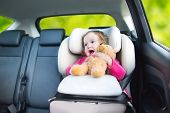 picture of car ride  - Cute Curly Toddler Girl With A Toy Bear Enjoying A Car Ride In A Safe Baby Seat - JPG