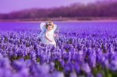 Cute Toddlger Girl In Fairy Costume Playing With Purple Flowers