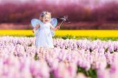 foto of fairies  - Portrait of an adorable toddler girl in a magic fairy costume and flower crown in her curly hair playing with a wand in a beautiful field of purple hyacinths in Keukenhof Holland on windy spring day