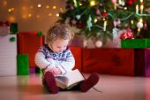 Little Girl Reading At Christmas Tree