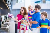 stock photo of little kids  - Big happy family with three kids traveling by airplane at Dusseldorf International airport parents with teenager boy toddler girl and little baby holding colorful luggage for summer beach vacation - JPG