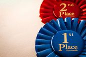 stock photo of rosettes  - 1st place blue winners rosette or badge to be awarded as a prize to the winner of a competition made of pleated blue ribbon with central text in gold with a 2nd place red rosette behind