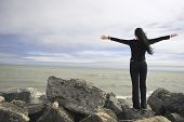 foto of mans-best-friend  - young woman enjoying the nature with her arms wide stretched