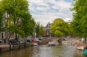 City View Of Amsterdam Canal, Bridge And Boats, Holland, Netherlands.