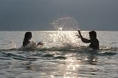 Teenage Girls Standing In The Water And Splashing Each Other, On A Summer Day In A Mountain Lake