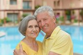 Senior couple standing by pool