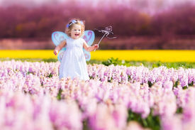 stock photo of princess crown  - Portrait of an adorable toddler girl in a magic fairy costume and flower crown in her curly hair playing with a wand in a beautiful field of purple hyacinths in Keukenhof Holland on windy spring day