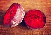 One beetroot divided into two. On wooden table.