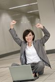 Cheerful business woman sitting and using laptop on ground.
