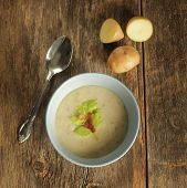 Top view of a potato soup in a blue bowl with fresh potatoes and spoon on a wooden background