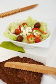 Closeup photo of healthy food. Fresh green salad and brown bread on white tabletop.