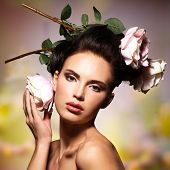 Beautiful  woman with pink flowers in hairs posing over creative color background. Fashion model with creative hairstyle