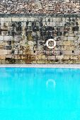 Conceptual Tranquil Old Swimming Pool with Clear Water, Emphasizing Lifebuoy Hanging on the Wall