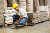Worker with sprained ankle on the floor in warehouse