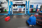 pic of garage  - Mechanic working on a tire wheel at the repair garage - JPG
