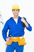 Portrait of happy electrician with wires against white background