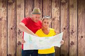stock photo of lost love  - Lost tourist couple using map against wooden planks background - JPG