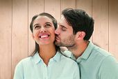Handsome man kissing girlfriend on cheek against wooden planks