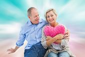 picture of girly  - Happy mature couple with heart pillow against digitally generated pink and blue girly design - JPG