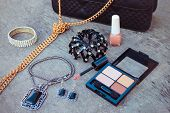 Women's accessories: eyeshadow, lip gloss, nail polish, clip hair, necklace, black handbag. Toned im