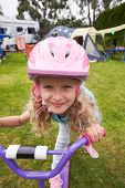stock photo of scooter  - Girl Riding Scooter Whilst On Family Camping Holiday  - JPG