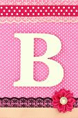 Wooden letter B on polka dots background