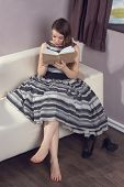 Young Woman Is Reading A Book