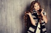 picture of jacket  - Fashion shot of a pretty teenager girl with beautiful long curly hair wearing white knitted dress and fur jacket - JPG