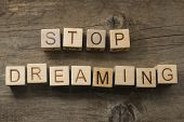STOP DREAMING text on a wooden background