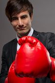 Fighting business man with boxing glove in studio.