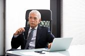 foto of 55-60 years old  - Half length portrait of a thoughtful businessman in the office with laptop computer and holding glasses - JPG