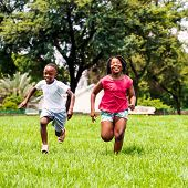 African Kids Running Together In Park.