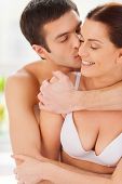 foto of cleavage  - Beautiful young loving couple sitting together in bed while man kissing his girlfriend and hugging her - JPG