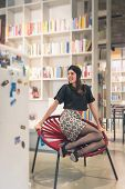 image of turban  - Beautiful young brunette with turban sitting in a bookstore - JPG