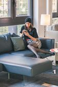 pic of turban  - Beautiful young brunette with turban texting on a couch - JPG