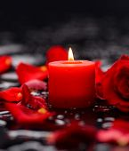 Beautiful red rose,petals with candle and therapy stones
