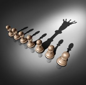 stock photo of leadership  - Leadership search and business recruitment concept as a group of pawn chess pieces and one individual standing out with a king crown cast shadow as a metaphor for the chosen one - JPG