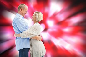 stock photo of male pattern baldness  - Happy mature couple hugging and smiling against valentines heart pattern - JPG